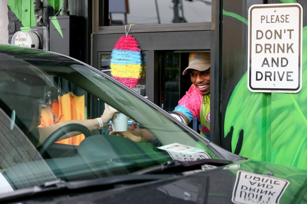 Owner Bernardo Baxter serves a frozen daiquiri to a customer in the drive-thru lane at SipIt Daiquiris To-Go, 1717 Pat Booker Road in Universal City, on Sunday, Apr. 5, 2020.